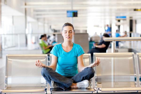 beautiful young casual woman doing yoga meditation at airport